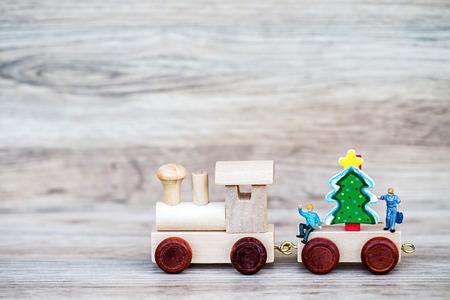 Miniatuur figuur Toy Houten Trein dragen kerstboom op houten achtergrond, Afbeelding voor kerstvakantie decoratief concept.