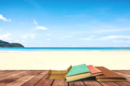 boom oud boek en grunge papier op houten platform naast tropisch strand en de blauwe zee op dag middaglicht.