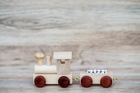 Het miniatuurobjecten van de Cijfer Houten Trein draagt Bloktekst Gelukkig over Houten Achtergrond, Beeld voor Concept.