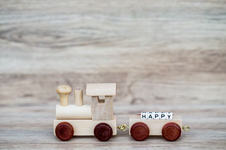 Miniature Figure Wood Train Toy Carry Block Text Happy Over Wooden Background, Image For Concept.