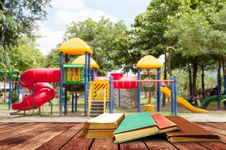 boom in de leeftijd boek en grunge papier op houten platform naast de speeltuin op de dag van de middag licht., terug naar school concept.