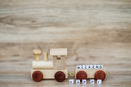 Miniature Figure Wood Train Toy Carry Block Text Happy weekend Over Wooden Background, Image For Concept. Imagens