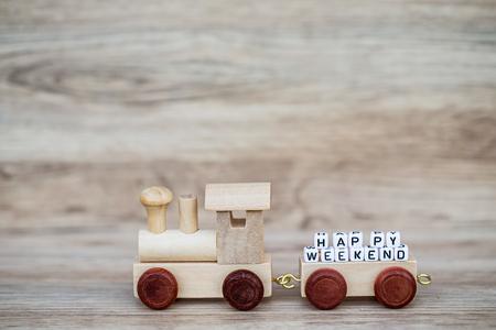 Miniatuur Houten de Treinstuk speelgoed van de Cijfer draagt ??Bloktekst Gelukkig weekend over Houten Achtergrond, Beeld voor Concept. Stockfoto