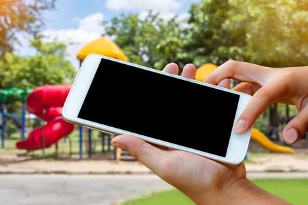 vrouw hand greep en aanraakscherm slimme telefoon, tablet, mobiel over wazig park en speeltuin achtergrond. Stockfoto