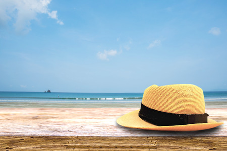 hat on on wood terrace over blue sea and tropical island beach background. Image for Summer Holiday Vacation concept.