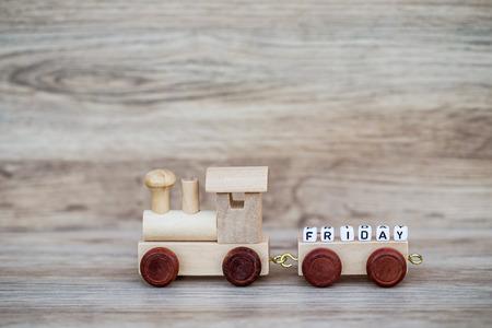 Het miniatuurobjecten van de Cijfer Houten Trein draagt Bloktekst Vrijdag over Houten Achtergrond, Beeld voor Concept. Stockfoto