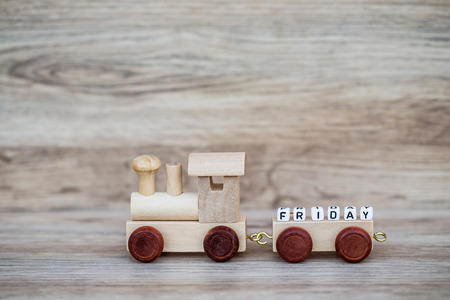 Miniature Figure Wood Train Toy Carry Block Text Friday Over Wooden Background, Image For Concept.