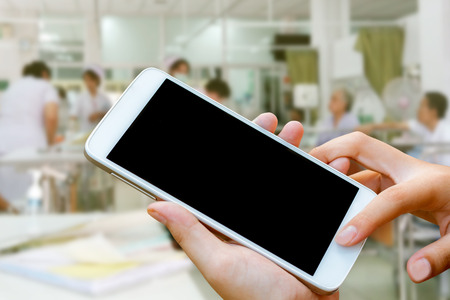 woman hand hold and touch screen smart phone, tablet,cellphone over blurred hospital background.