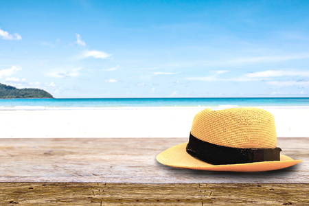 bussines people: hat on on wood terrace over blue sea and tropical island beach background. Image for Summer Holiday Vacation concept.