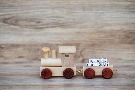Het miniatuurobjecten van de Cijfer Houten Trein draagt ??de Zwarte Vrijdag van de Bloktekst over Houten Achtergrond, Beeld voor Concept.