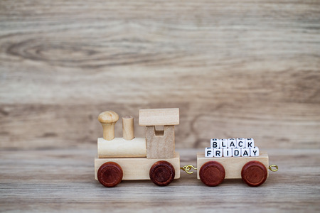 Miniature Figure Wood Train Toy Carry Block Text Black friday Over Wooden Background, Image For Concept. Imagens