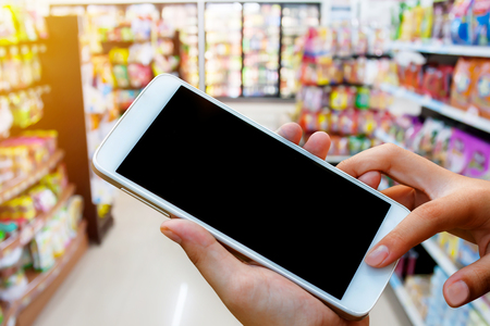 woman hand hold and touch screen smart phone, tablet,cellphone over blurred shopping center or super market background.