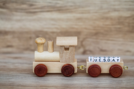 Miniature Figure Wood Train Toy Carry Block Text Tuesday Over Wooden Background, Image For Concept. Imagens