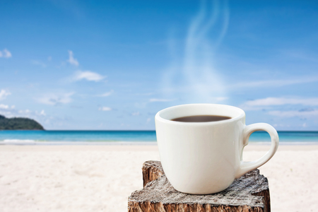 white cup of coffee on white sand beach over blue sky and sea on day noon light background.