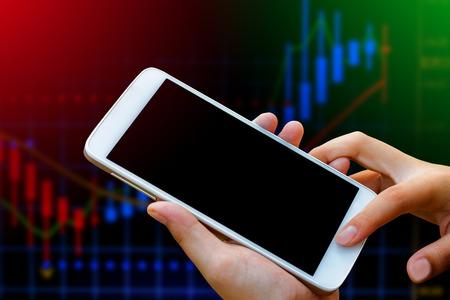 zakenvrouw hand houden en touch screen op smartphone, tablet, mobiele telefoon dan vervagen grafiek beurs achtergrond, met gefilterd rode en groene kleur, abstracte achtergrond op forex en aandelen concept. Stockfoto