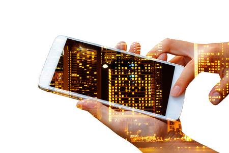 dubbele belichting van de greep van de vrouwenhand en de slimme telefoon van het aanrakingsscherm, tablet, cellphone over de lichte achtergrond van de stadsnacht. Stockfoto