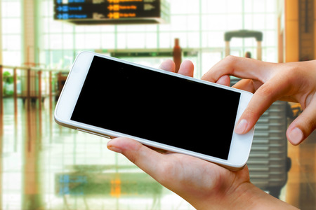 woman hand hold and touch screen smart phone,tablet,cellphone in the airport terminal