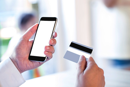 Business Man Hand Hold Smart phone or Cellphone with Credit Card over blurred family at home, Image for Solution of Mobile banking Shopping or Mobile Payment Application online concept. Imagens