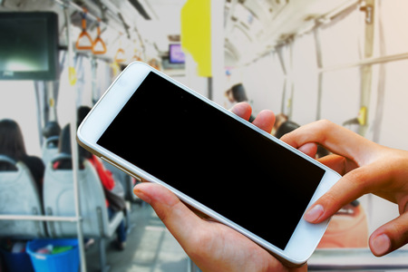 woman hand hold and touch screen smart phone, tablet,cellphone on city metro bus in morning background.