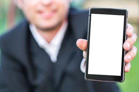 Slimme telefoon met lege ruimte op Hand van Kaukasische business man die cellphone over Wazig tuin outdoor achtergrond. Afbeelding voor reclame online Application Solution of Mobile Banking-concept.