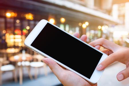 vrouw hand greep en aanraakscherm slimme telefoon, tablet, mobiel over wazig restaurant achtergrond.