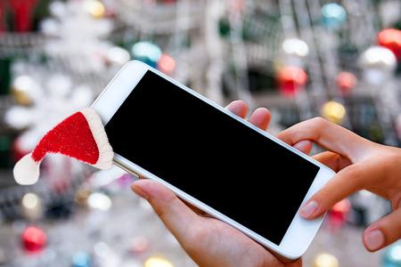 vrouw hand houden en touchscreen slimme telefoon, tablet, mobiel met Santa dop over kerstversiering, abstracte achtergrond van oplossing van vakantie communicatie of reclame.