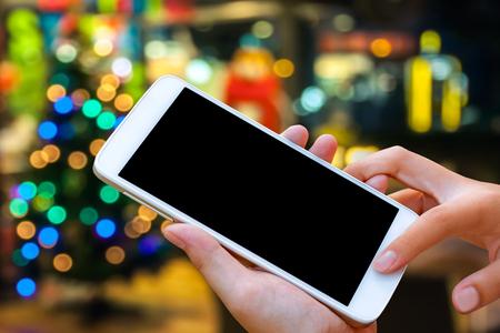 vrouwelijke handgreep en touch screen slimme telefoon, tablet, mobiele telefoon over kerstversieringen. Stockfoto
