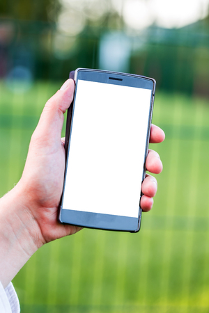 Smartphone with blank space on Hand of Caucasian Business Man holding Cellphone over Blurred garden outdoor background. Image for Advertising online Application Solution or Mobile banking Concept. Imagens