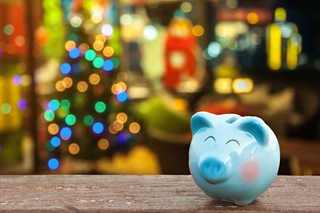 geld te besparen op kerstvakantie, metafoor door spaarvarken met kerstversiering achtergrond, voor de tijd om te sparen of de oplossing starten om geld te besparen voor de kerst vakantie viering begrip ..