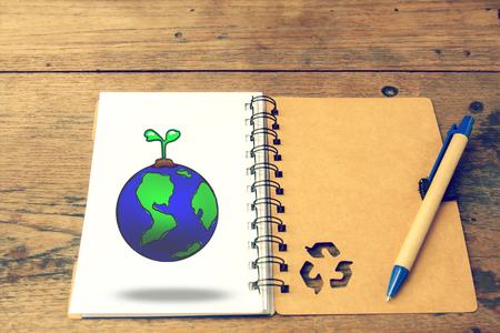wereldbol met recycle notebook en pen op houten achtergrond, vintage kleurtoon. aarde dag concept.