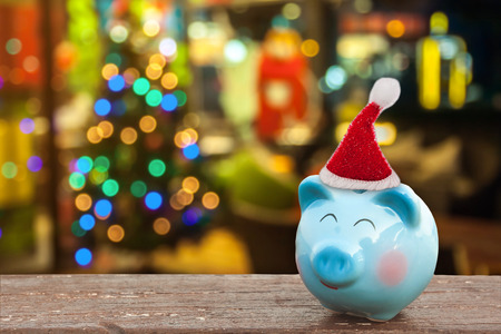 piggy bank with Santa hat on wooden table over Christmas decoration background, abstract background to time to start to saving or solution for keep money for celebration. Stock Photo