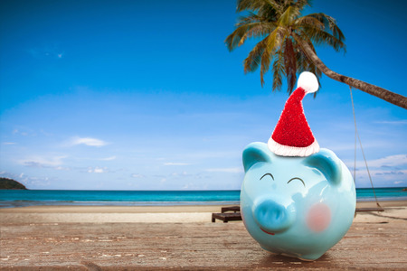 summer piggy bank with Santa hat on the beach,summer holiday.