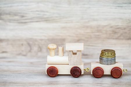Miniatuurcijfer Wood Train Toy Carry Euromunten over houten achtergrond, imago voor geld Concept.