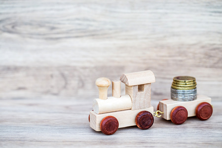 tiny: Miniature Figure Wood Train Toy Carry Euro Coins Over Wooden Background, Image For Money Concept.