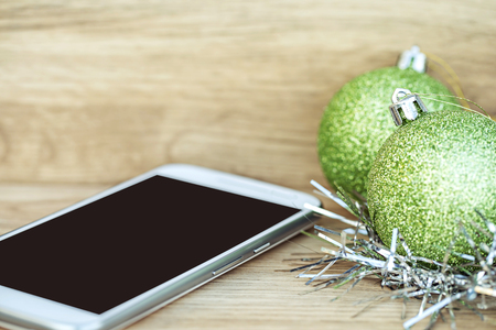 Christmas Decoration on wooden floor with Christmas glitter ball and smartphone, Image for Christmas Holiday Concept.