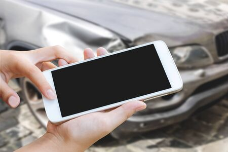 woman hand hold and touch screen smart phone or cellphone over blurred of car accident background. Stock fotó