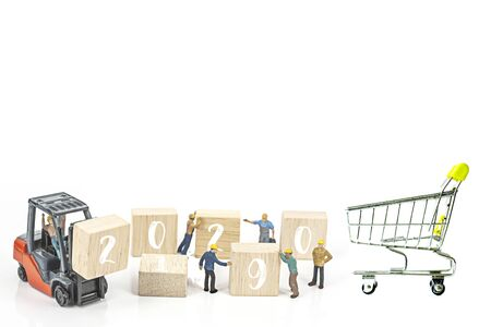 miniature worker team building standing front of forklift machine with white 2020 number on wooden block on white background, decoration to Happy new year 2020 concept.