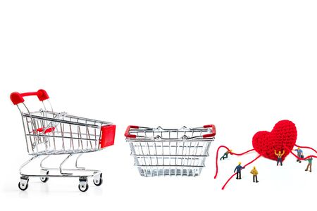 miniature worker holding robe heart shape with shopping cart on white background 免版税图像