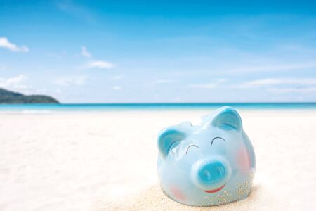 Summer happy piggy bank on sand beach over blurred tropical blue sea  background, Image for saving vacation concept.