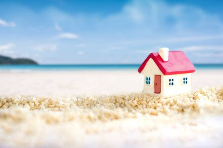 miniature house with red roof on tropical sand beach over blurred clear sky on day noon light.Image for property real estate investment concept. Reklamní fotografie