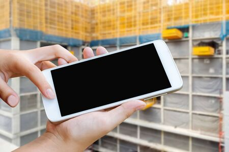 woman hand hold and touch screen smart phone or cellphone over blurred building construction background,