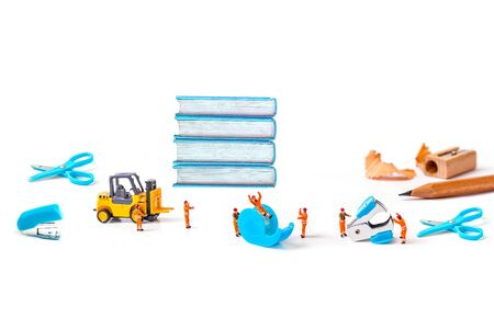 selective focus of miniature workers man with stationery isolated on white background, Reklamní fotografie