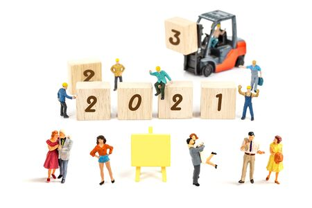 miniature worker team building standing front of forklift machine with   2021 number on wooden block on white background decoration to Happy new year 2021 concept.