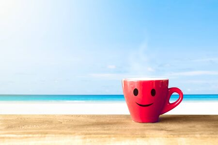 cup of coffee on wooden table over blue sky and sea on day noon light background.