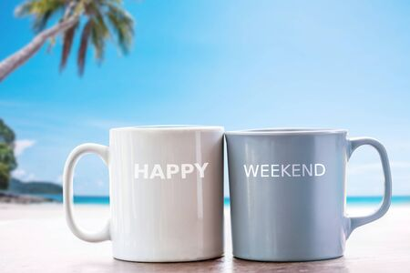 two cup of coffee with happy weekend text on white sand beach with blue sea and cloudy blue  sky on day noon light background, image for happy weekend concept.