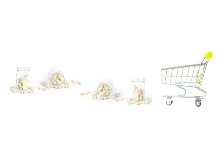 shopping cart with herb capsule pills spilling out off bottle isolated on white background.Image for Medical Concept.