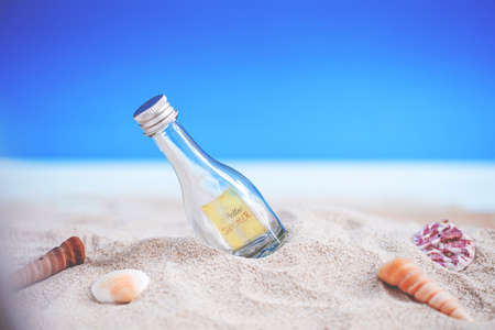 bottle on sand beach with seashell over blurred tropical blue sea and clear blue sky Standard-Bild