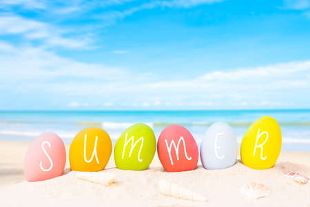 colorful eggs on white sand beach over blue background,happy Easter or summer holiday concept.