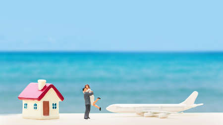 selective focus of miniature tourist couple with plastic toy airplane and home model over blurred swimming pool ,abstract background to saving money for travel concept