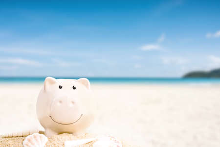 summer happy piggy bank on sand beach over blurred tropical blue sea background, image saving vacation concept.